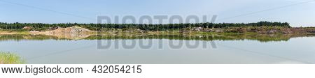 Shallow Lake On The Site Of The Abandoned Quarry Of Ilmenite Ore With Dumps And Forest On A Opposite
