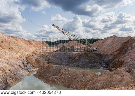 Boom Walking Excavator Digs Exposed Stratum Of Ilmenite Ore In Quarry Among The Waste Rock Dumps Aga