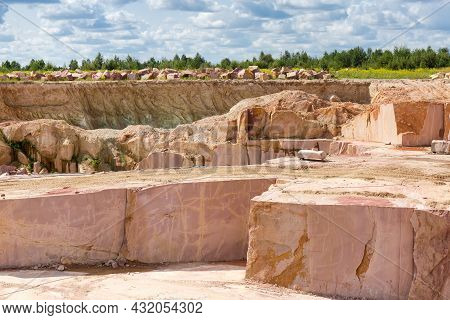 Stratums Of Mining Red Granite In Operating Quarry Against The Quarry Slope And Sky In Summer Day