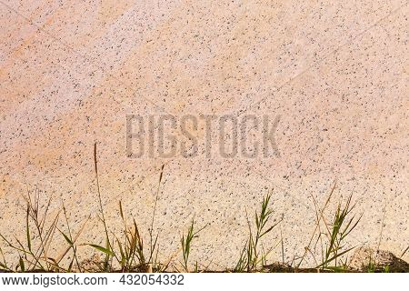 Flat Edge Of The Block Of Pink Granite After Working Of The Stone Cutting Tool, With Grass At The Bo