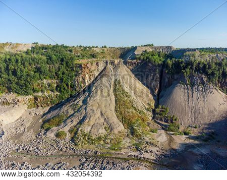 Steep Slope Of Quarry For The Extraction Of Gray Granite, Partly Overgrown With Forest, Old Waste Ro