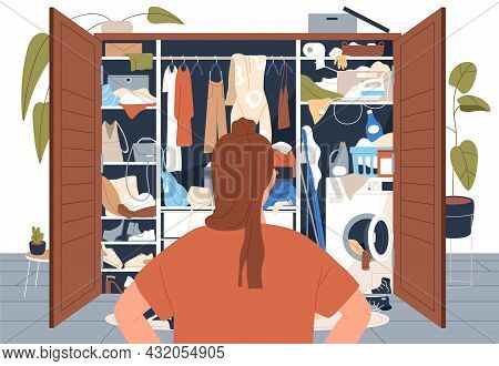 Woman Stand In Front Of Messy Untidy Wardrobe. Person Look At Open Closet Full Of Disordered Clothes