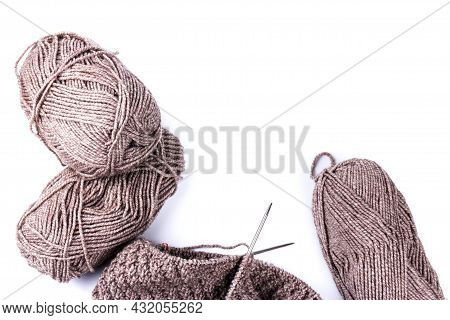 Knitting Needles And Dark Grey Woolen Threads On White Background. Natural Wool Knitting Background