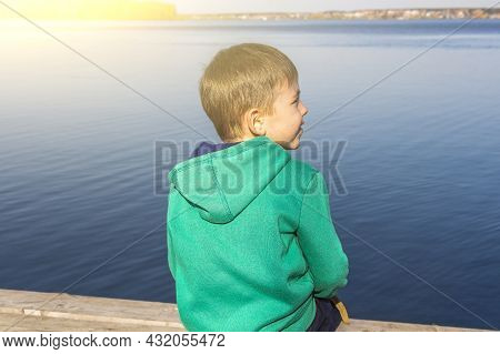 Adorable Child Boy Looks Into Distance Of Lake. Autumn Landscape. Pensive Thinking Child. Young Trav