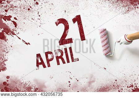 April 21st . Day 21 Of Month, Calendar Date. The Hand Holds A Roller With Red Paint And Writes A Cal