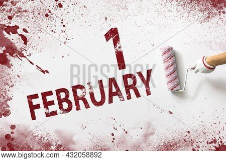 February 1st . Day 1 Of Month, Calendar Date. The Hand Holds A Roller With Red Paint And Writes A Ca