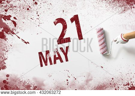 May 21st . Day 21 Of Month, Calendar Date. The Hand Holds A Roller With Red Paint And Writes A Calen