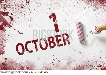 October 1st . Day 1 Of Month, Calendar Date. The Hand Holds A Roller With Red Paint And Writes A Cal