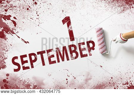 September 1st . Day 1 Of Month, Calendar Date. The Hand Holds A Roller With Red Paint And Writes A C