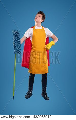 Self Assured Young Housekeeper With Superhero Cape Holding Hand On Waist And Looking Up While Standi
