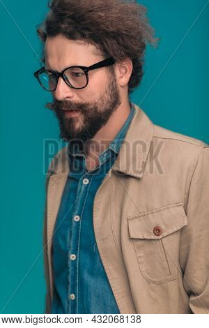 portrait of curly hair man with glasses and long beard looking away while posing on blue background in studio