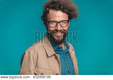 portrait of enthusiastic unshaved guy with glasses in beige jacket and denim shirt smiling and posing on blue background in studio