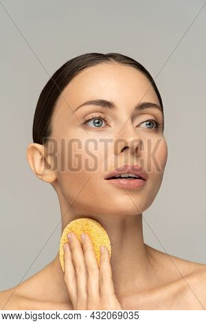 Young Woman With Nude Make-up And Naked Shoulders Cleaning Neck With Exfoliating Sponge Isolated On