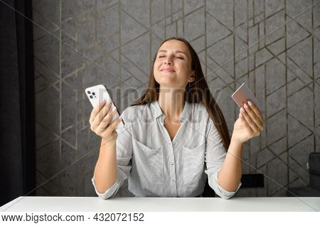 Inspired Young Woman Holding Credit Card And Smartphone, Dreaming, Imagines Long Awaited Purchases,