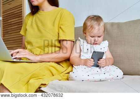 Faceless Modern Mother Typing On Computer While Serious Little Toddler Browsing Cellphone. Concept O