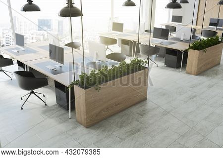 Contemporary Coworking Office Interior With Equipment, Furniture, Daylight, Shadows And Wooden Floor
