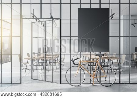 Modern Glass Partition And Bike In Stylish Coworking Office Interior With Empty Black Mock Up Poster