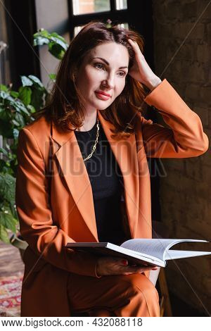 Attractive Young Woman In A Business Terracotta Jacket Sits With A Book In Her Hands And Straightens