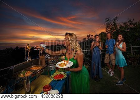 Group of friends having ?furshet in the backyard at summer sunset. Young woman putting food on a plate
