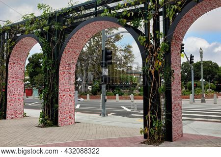 LOS ANGELES, CALIFORNIA - 18 AUG 2021:  Arches at LA Plaza Paseo Walkway. The block-long pathway between the LA Plaza museum and the historic La Placita Church, includes historical signage.