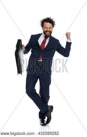 young businessman crossing his legs, celebrating succes and holding a briefcase against white background