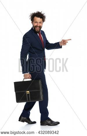 side view of a young businessman walking and pointing to the side and holding a briefcase