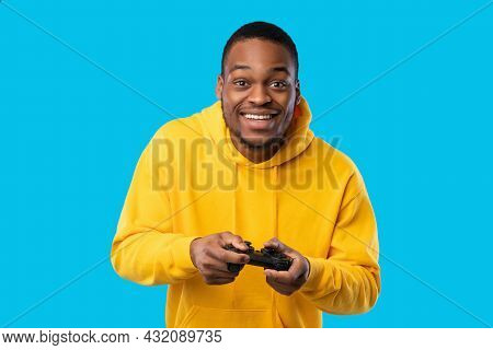 Cheerful Black Guy Playing Videogame Holding Game Controller, Blue Background