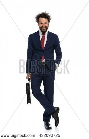 handsome businessman holding one hand in pocket, crossing his legs, holding a briefcase and smiling