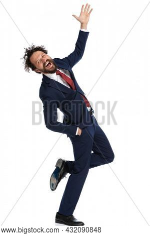 young businessman crossing his legs, raising his hand, leaning backwards and smiling on white background