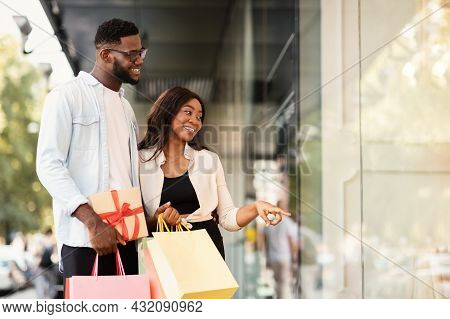 Portrait Of Black Couple With Shopping Bags Pointing At Window