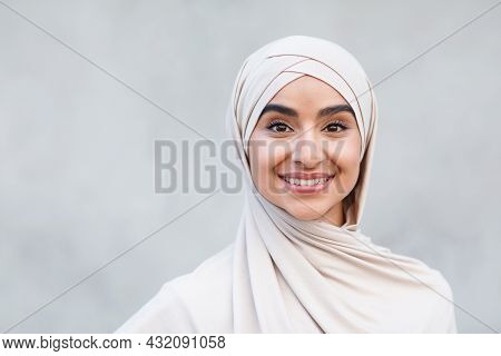 Portrait Of Cheerful Cute Attractive Young Arabian Islamic Female In Hijab Looks At Camera