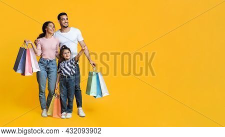 Shopping Offer. Arab Family Of Three Carrying Shopper Bags And Pointing Aside
