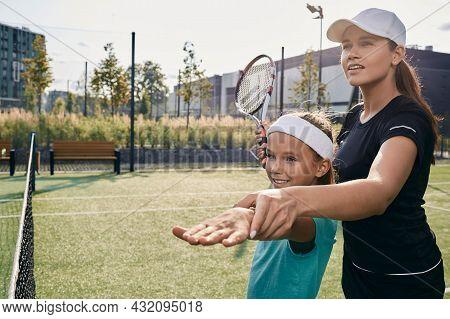 Female Tennis Coach Teaches Little Girl To Play Tennis On Grass Court. Tennis Lesson For A Child