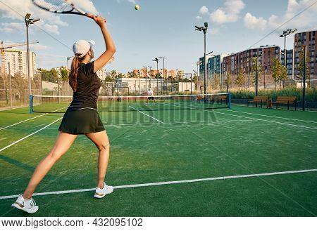 Tennis Player Serves Ball While Playing Match With Her Male Partner On A Grass Court In Urban Enviro