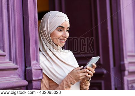 Smiling Pretty Cute Young Muslim Arabian Female In Hijab Enjoys Free Time At Weekend And Checks Soci