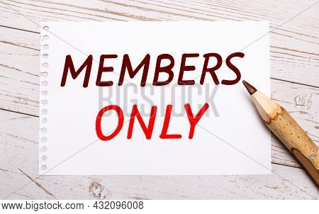 On A Light Wooden Background, A Colored Pencil And A White Sheet Of Paper With The Text Members Only