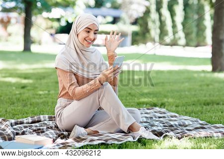 Happy Young Arabian Muslim Woman In Hijab Calls On Smartphone, Video Meeting In Green Park