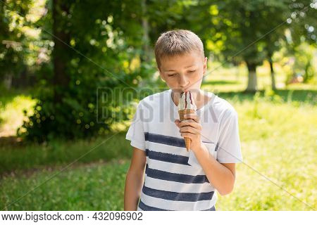 Teenager Boy Eating Ice-cream Cone On Green Nature Background. Summer, Junk Food And People Concept.