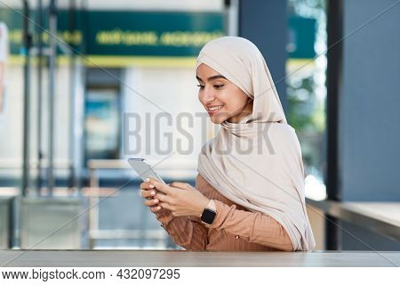 Smiling Cute Young Arabian Islamic Woman In Hijab Texting Message, Checking App And Social Media