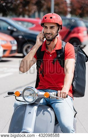 Smiling Arabian Deliveryman With Thermo Backpack Talking On Smartphone While Riding Scooter