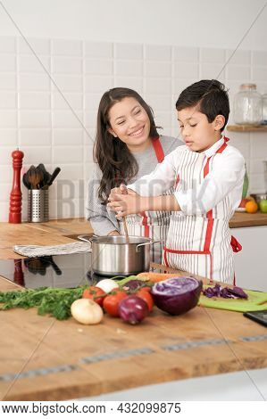 Mother Teaches Her Son How To Cook Healthy Food In The Kitchen. Lifestyle With Latin People. Child L