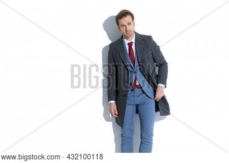 cool sexy fashion model arranging his coat and looking away against white background
