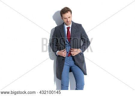 attractive businessman arranging his coat, looking down and posing against white background