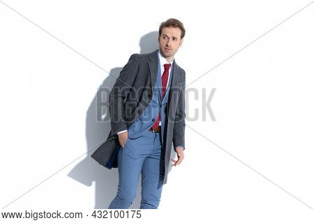 cool businessman posing with one hand in pocket and looking away in a fashion pose