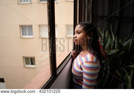African American Girl Near The Window. From Home Looking Outside With A Smile.