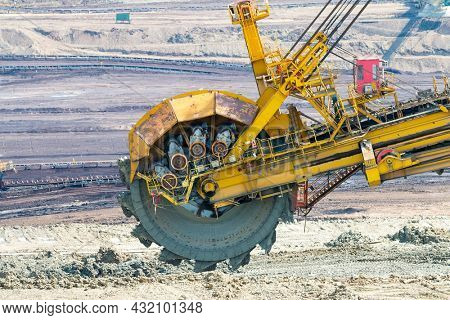 Bucket wheel excavator at work in coal mine. Mining industry from above. Open pit in Central Europe. Heavy industry before Green deal.