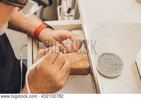 Close-up View Of A Hands Of A Professional Using Wax To Mould The Pieces Of A Dental Mould In A Labo