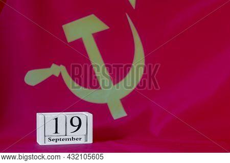 September 19 On A Wooden Calendar Against The Background Of The Communist Party Flag.september 19 El