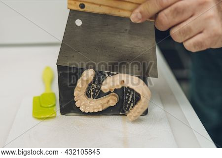 Close-up View Of The Hands Of A Man Detaching A Mould Made With A 3d Printer From The Base Of The Pr