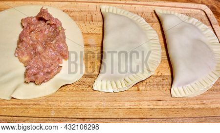 Making Pies With Meat In Her Home Kitchen. Raw Dough And Meat For Baking In The Oven, Process Of Mak